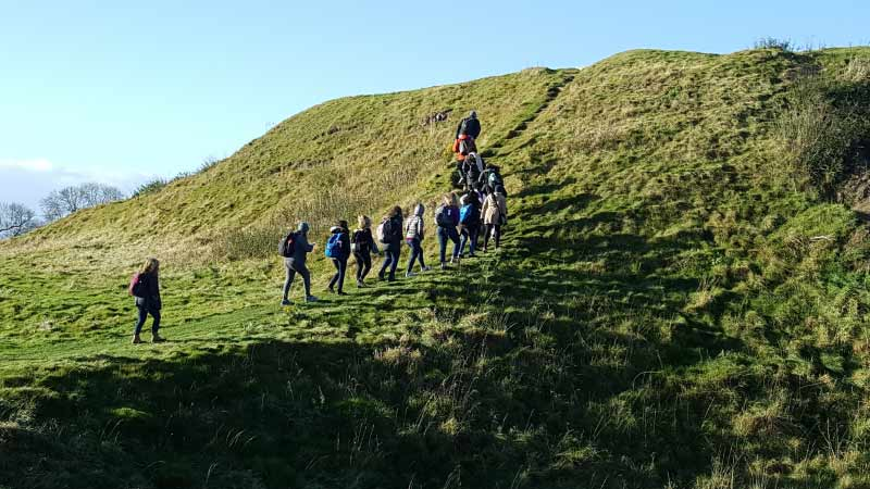 People hiking up a green hill in Fotheringhay